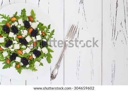 Summer green salad with arugula, melon, blackberries, almonds and feta cheese. Copy space background - stock photo