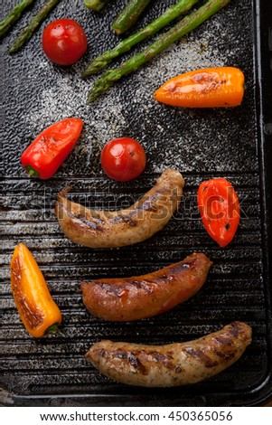 Summer grill - grilled sausages and assorted grilled vegetables - asparagus, mini pepper, and tomatoes - on griddle.