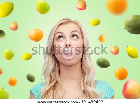 summer, healthy eating, emotions, expressions and people concept - happy young woman or teenage girl chewing gum over green background with fruits - stock photo