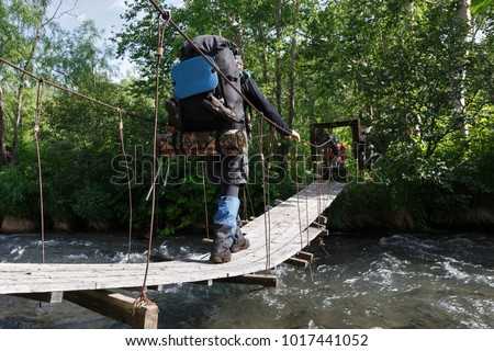 Summer hiking on Kamchatka Peninsula: tourist and traveler with backpack behind his shoulders crossing mountain river in forest on pedestrian suspension bridge. , Russian Far East, Kamchatka Region