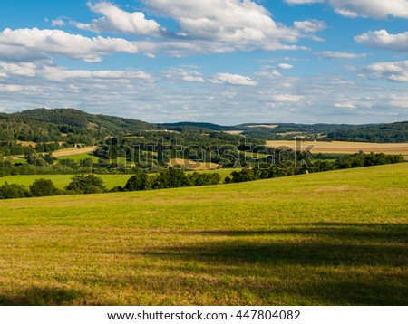 Summer hilly landscape withe green field, forests, blue sky and white clouds, Central Bohemia, Czech Republic