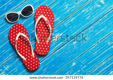 Summer holiday background, Beach accessories on white wood table, Vacation and travel items, Red flip flop with sunglasses on wood table - stock photo