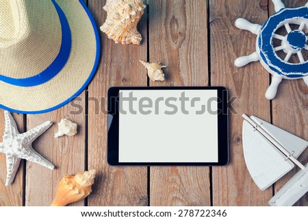 Summer holiday background with digital tablet on wooden table. View from above - stock photo