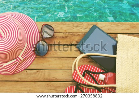Summer holiday bag with tablet and flip flops on wooden deck. View from above - stock photo