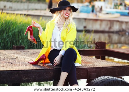 Summer holiday concept. Beautiful young woman sitting on the bridge, take of her red high hills shoes and enjoying good weather. - stock photo