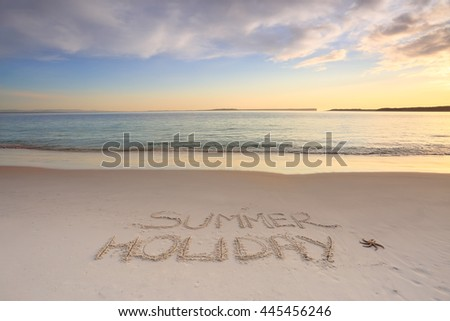 Summer holiday etched into the sand on the shoreline of a beach with early morning light.
