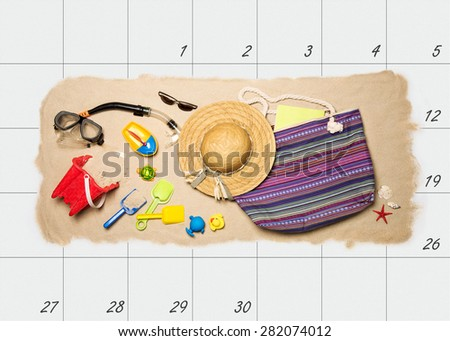 Summer holiday planning. Summer beach accessories on top of monthly calendar