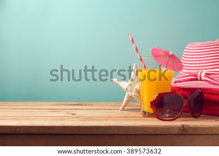 Summer holiday vacation concept with orange juice and beach items - stock photo