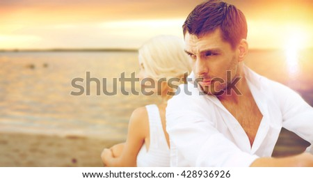 summer holidays and dating concept - couple sitting at sea side