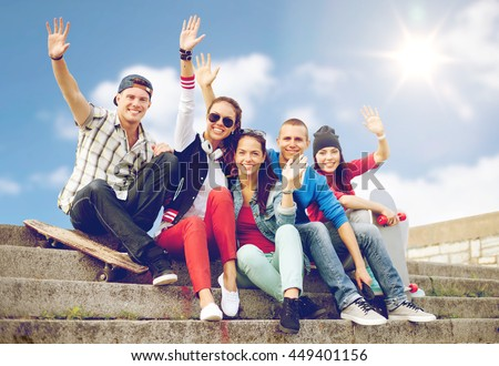 summer holidays and teenage concept - group of smiling teenagers hanging outside and waving hands