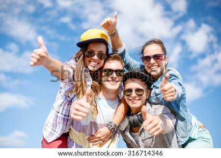 summer holidays and teenage concept - group of smiling teenagers in sunglasses hanging outside and showing thumbs up - stock photo