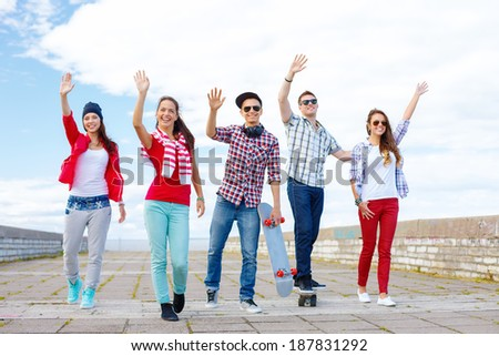summer holidays and teenage concept - group of smiling teenagers waving hands outside - stock photo