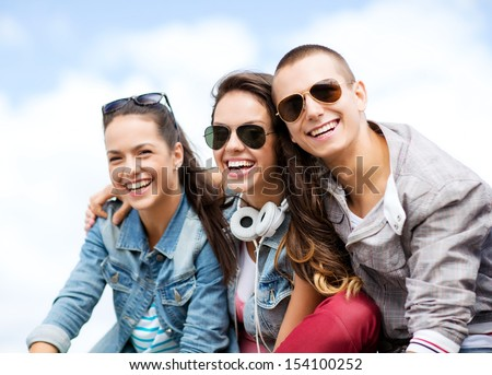 summer holidays and teenage concept - group of teenagers hanging outside - stock photo