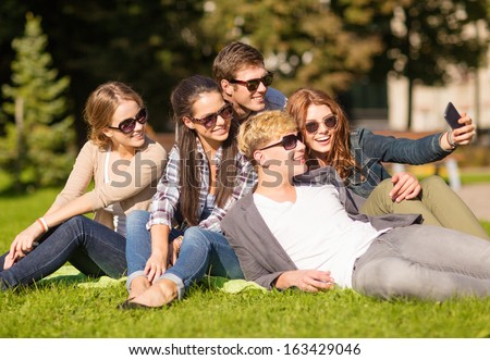 summer holidays and teenage concept - group of teenagers taking selfie in park with smartphone - stock photo