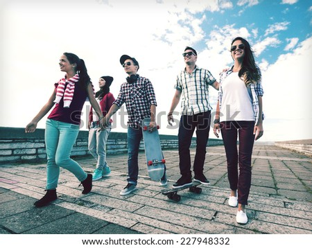summer holidays and teenage concept - group of teenagers with skates outside - stock photo
