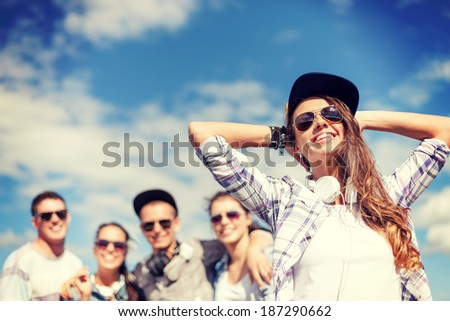 summer holidays and teenage concept - teenage girl in sunglasses, cap and headphones hanging out with friends outside - stock photo