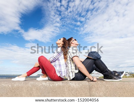 summer holidays and teenage concept - teenagers sitting back to back and looking up in the sky - stock photo