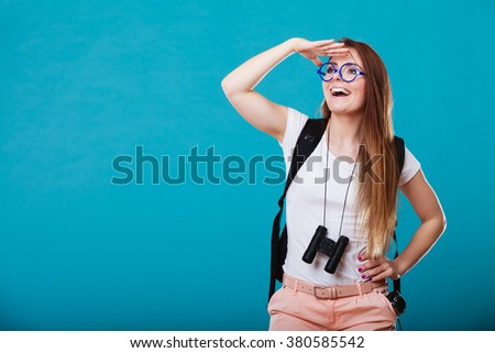 Summer holidays and tourism concept. Attractive woman long hair with backpack holding binocular on blue - stock photo