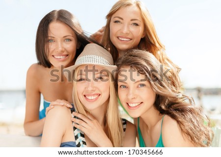 summer holidays and vacation concept - group of smiling girls in cafe on the beach - stock photo