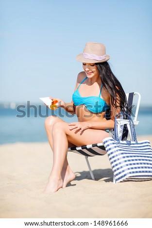 summer holidays and vacation - girl applying sun protection cream - stock photo