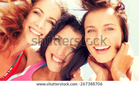 summer holidays and vacation - girls faces with shades looking down - stock photo