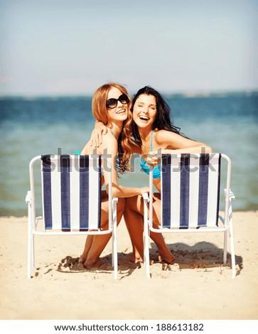 summer holidays and vacation - girls in bikinis sunbathing on the beach chairs - stock photo