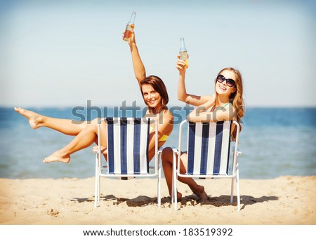 summer holidays and vacation - girls sunbathing and drinking on the beach chairs - stock photo