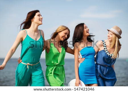 summer holidays and vacation - girls walking on the beach - stock photo