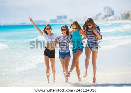 summer holidays and vacation - girls walking on the beach laughing. summer holidays and vacation - group of girls chilling on the beach near the ocean. girls having fun on the beach
