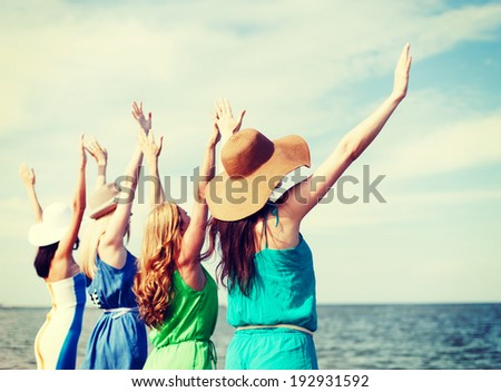 summer holidays and vacation - girls with hands up on the beach - stock photo