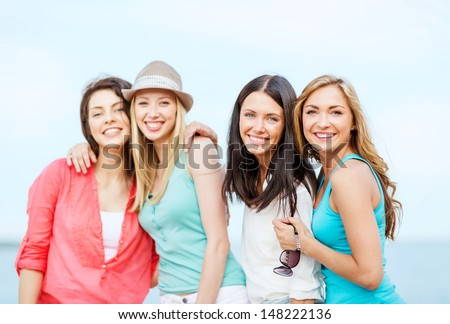 summer holidays and vacation - group of girls chilling on the beach - stock photo