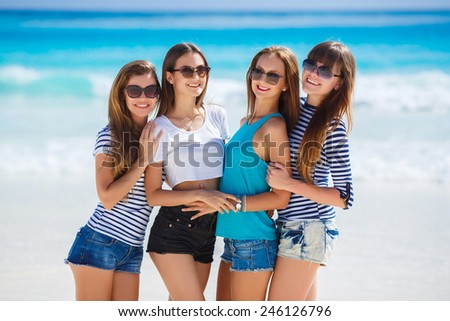 summer holidays and vacation - group of girls having fun on the beach. Young fun people are having good time on the ocean beach. Caribbean sea. group of girls chilling on the beach - stock photo
