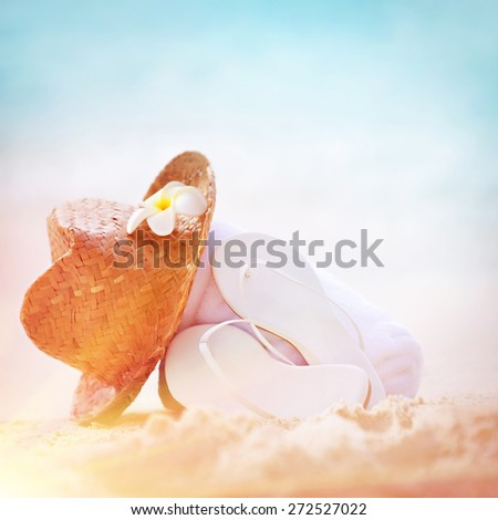 Summer holidays background, closeup photo of stylish beach clothing on sandy seashore, nice straw hat white flip flops, necessary accessories for summer vacation on beach resort - stock photo