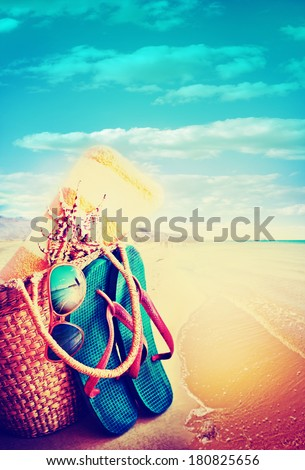 Summer holidays bag, sun glasses and flip flops on a tropical beach - stock photo