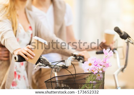 summer holidays, bikes, love, relationship and dating concept - closeup of couple holding coffee and riding bicycle - stock photo