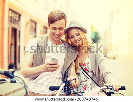 summer holidays, bikes, love, relationship, navigation, gps and dating concept - couple with bicycles and smartphone in the city