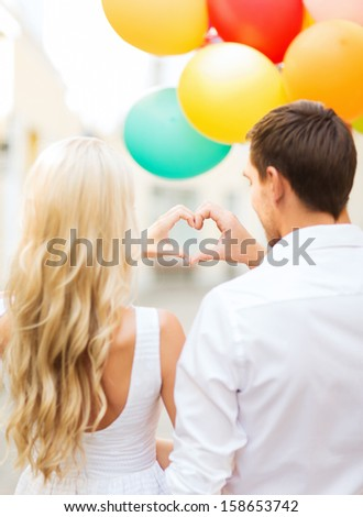 summer holidays, celebration and dating concept - couple with colorful balloons making heart shape in the city - stock photo