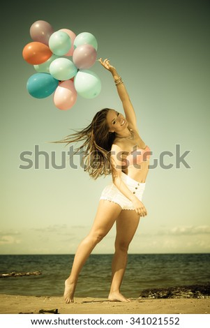 Summer holidays, celebration and lifestyle concept - attractive athletic woman teen girl with colorful balloons outside on beach seashore background. Aged vintage tone - stock photo