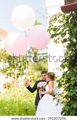 summer holidays, celebration and wedding concept - couple with colorful balloons