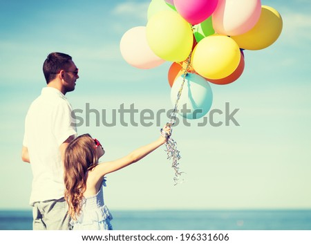 summer holidays, celebration, children and family concept - father and daughter with colorful balloons - stock photo