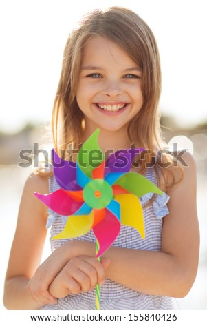 summer holidays, celebration, family, children and people concept - happy girl with colorful pinwheel toy - stock photo