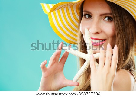 Summer holidays concept. Closeup woman in yellow hat holding white shell starfish in hand on vivid blue background