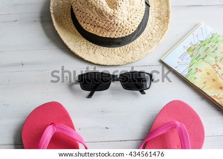 Summer holidays concept - Getting ready - Sunglasses, flip flops, map and straw hat on wooden table - stock photo