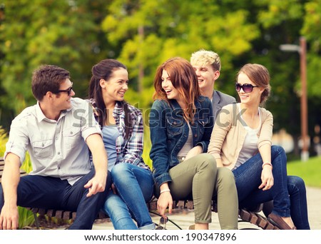 summer holidays, education, campus and teenage concept - group of students or teenagers hanging out - stock photo