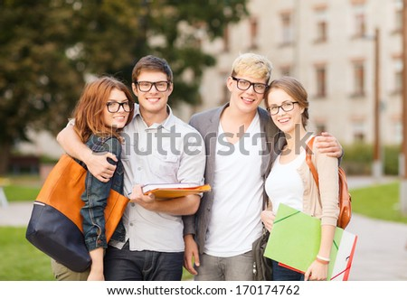 summer holidays, education, campus and teenage concept - group of students or teenagers with files, folders and eyeglasses hanging out - stock photo