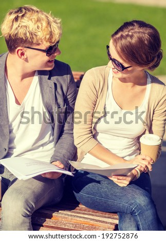 summer holidays, education, campus and teenage concept - smiling boy and girl with books, notebooks, files and folders - stock photo