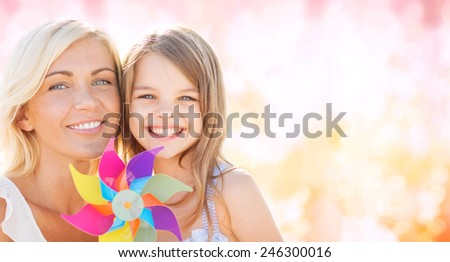 summer holidays, family, children and people concept - happy mother and girl with pinwheel toy over pink lights background - stock photo