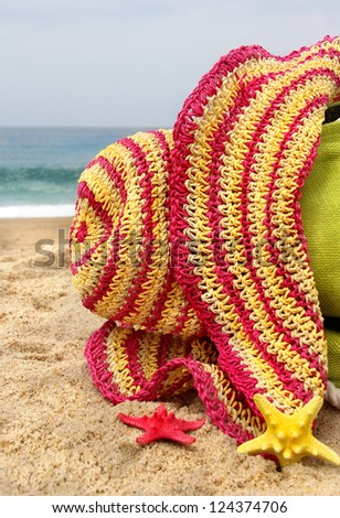 Summer holidays - green beach bag on the seacoast, pink straw hat and funny sea stars - stock photo