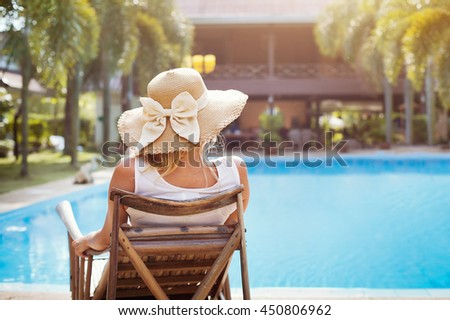 summer holidays in luxury hotel, woman relaxing near beautiful swimming pool - stock photo