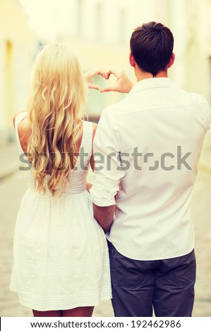 summer holidays, love, travel, tourism, relationship and dating concept - romantic couple in the city making heart shape